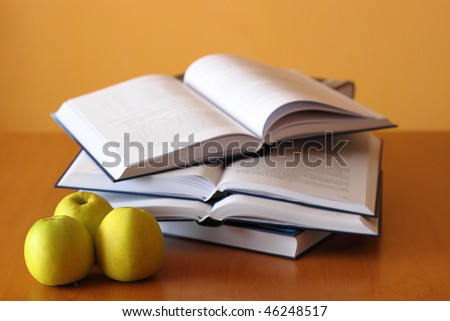 three green apples and four opened books on the desk - stock photo
