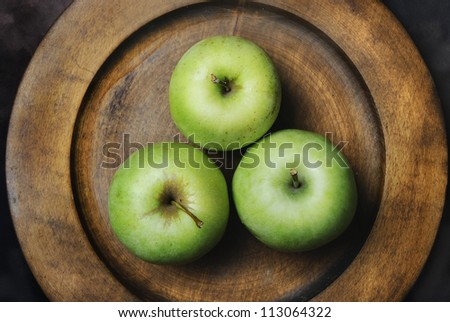 Three green apples in wooden plate - stock photo