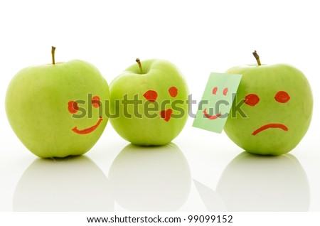 Three green apples, smiling and crying on white.