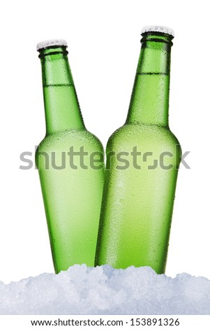 Three green beer bottles sitting on ice over a white background.