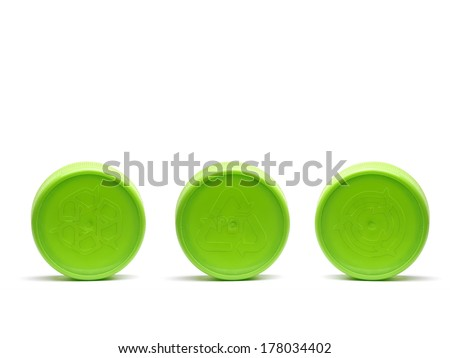 Three green plastic caps with different recycle symbols embossed shot on white - stock photo