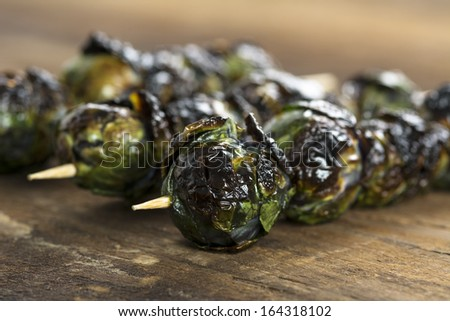 Three grilled organic purple Brussels sprouts on skewers set on wood - stock photo