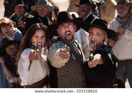 Three gunfighters yell while shooting in outdoor old west scene - stock photo