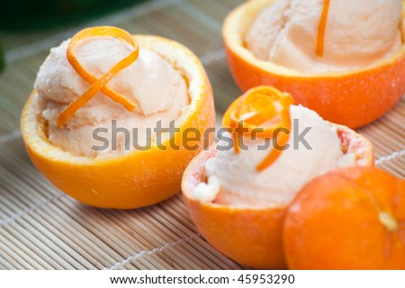 Three hallowed oranges filled with fresh italian orange sorbet on a japanese towel. - stock photo