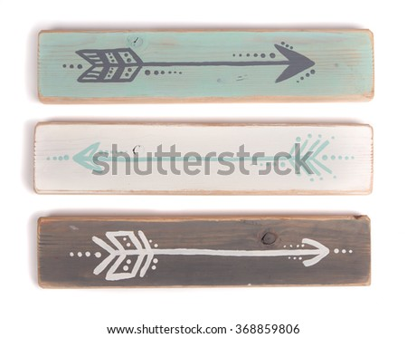 Three hand painted arrows on a wooden plank on a white background - stock photo