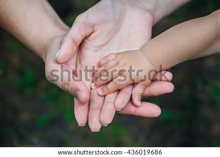 Three hands of the same family - father, mother and baby stay together. Close-up. The concept of family unity, protection, support, prosperity, love and parental happiness. - stock photo
