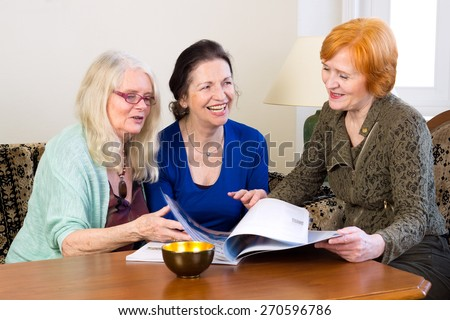 Three Happy Adult Female Friends Enjoying at Home While Scanning a Magazine on the Table. - stock photo