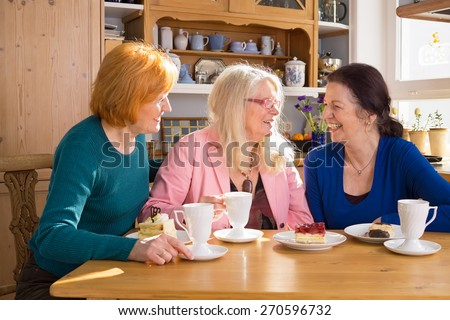 Three Happy Adult Female Friends Having Cups of Tea or Coffee and Slices of Cakes at the Wooden Table While Talking Funny Moments. - stock photo