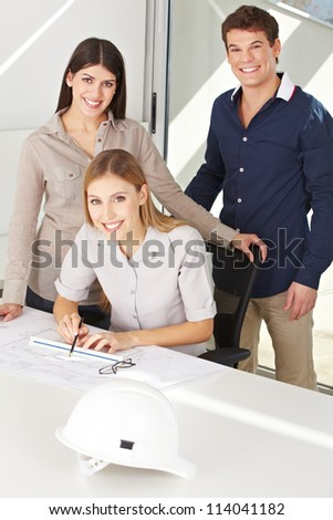 Three happy architects with construction drawing in their office - stock photo