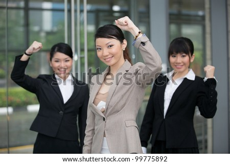 Three happy Asian business women standing in row. - stock photo