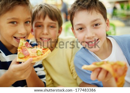 Three happy boys enjoying pizza - stock photo