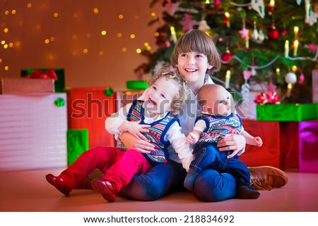 Three happy children, brothers and sister sitting under a Christmas tree, boy holding a little toddler girl and funny baby, kids ready to open Xmas presents - stock photo