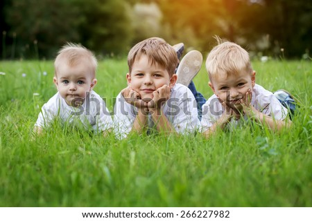 Three happy children (brothers)  resting on the green grass  - stock photo