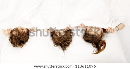 Three happy children in the bed - stock photo
