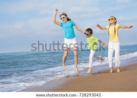 Three happy children jumping on the beach at the day time. People having fun outdoors. Concept of friendly family and of summer vacation.