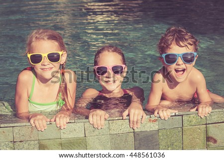 Three happy children playing on the swimming pool at the day time. Kids having fun outdoors. Concept of friendly family. - stock photo