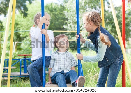 Three happy children playing on the swing at the day time - stock photo