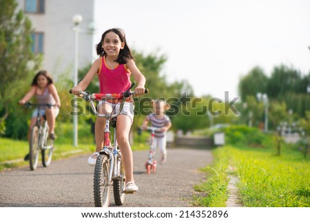 Three happy children riding on bicycle - stock photo