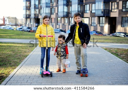 three happy children school aged girl and boy ant toddler boy on the city street - stock photo