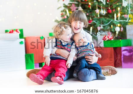 Three happy children - teenager boy, toddler girl and their newborn baby brother - playing together under a beautiful Christmas tree - stock photo