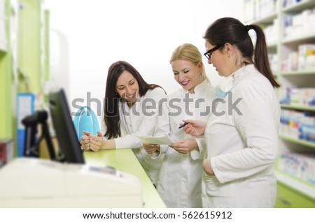 Three happy female pharmacists at work. looking at prescription, selective focus on last girl in row