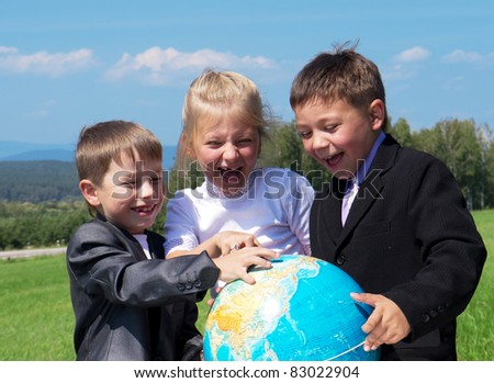 three happy friends holding earth globe, green meadow at background - stock photo