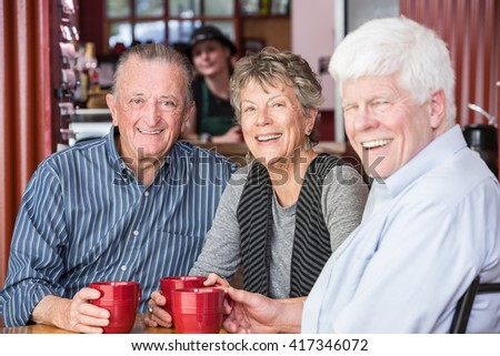 Three happy friends in a coffee house - stock photo