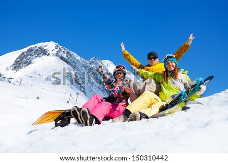 Three happy friends man and women sit in snow with snowboards lifting and waving hands - stock photo