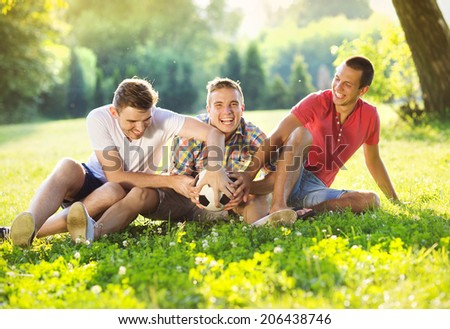 Three happy friends spending free time together in park sitting on grass, playing with soccer ball - stock photo