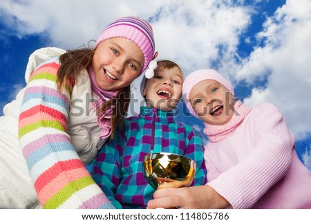 three happy friends with award on sky background - stock photo