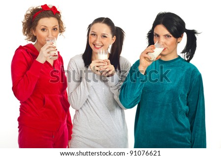 Three happy friends women in pajamas drinking milk isolated on white background - stock photo