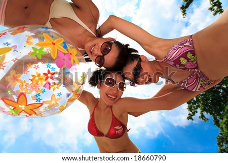 three happy girls friends at the beach on a beautiful day