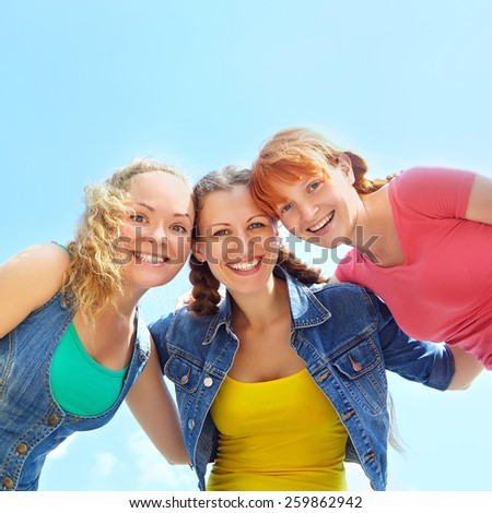 Three happy girls looking at camera and laughing. girls embracing. view from below.
