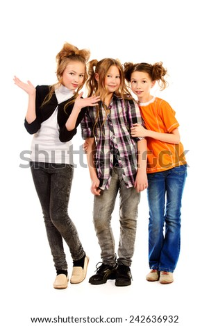 Three happy girls standing together and smiling at camera. Isolated over white. - stock photo