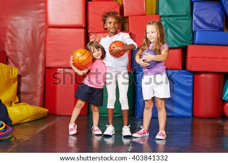 Three happy girls standing with balls in a gym of a preschool - stock photo
