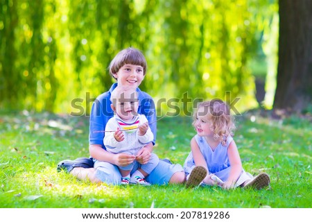 Three happy kids, brothers and sister, laughing teenager boy, little baby and a funny curly girl playing together with flowers in a sunny garden of their backyard  on a warm sunny day