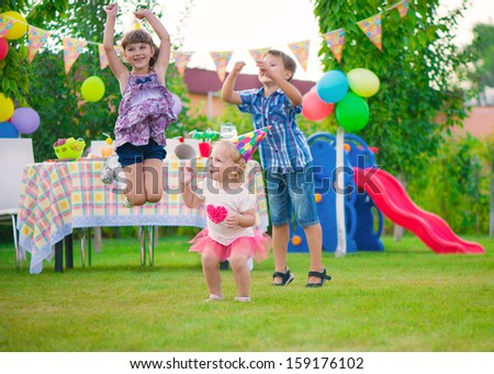 Three happy kids dancing during birthday party - stock photo