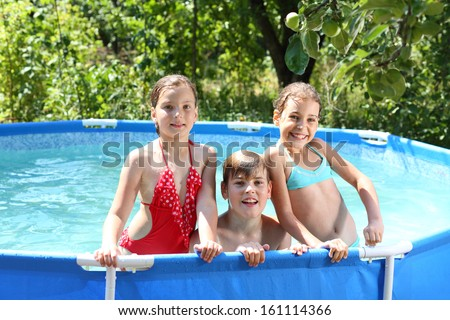 Three happy kids having fun in swimming pool on the courtyard outdoor - stock photo