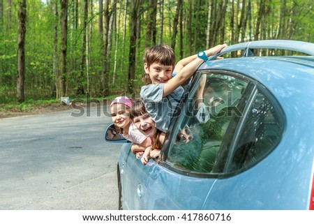 three happy kids in car, family trip, summer vacation travel - stock photo