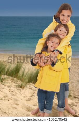 Three happy kids in raincoats on the beach - stock photo