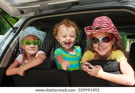 three happy kids in the car - stock photo