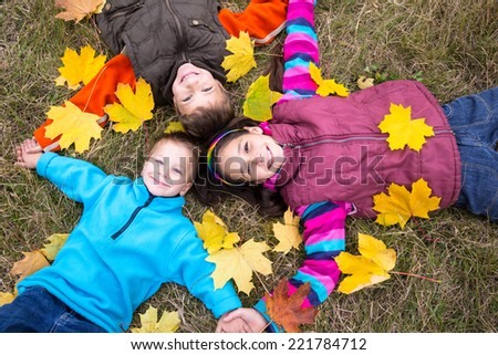 Three happy kids lying together on ground with yellow leaves, outdoors - stock photo
