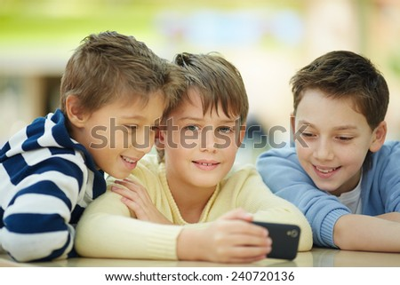 Three happy little boys sitting in cafe - stock photo