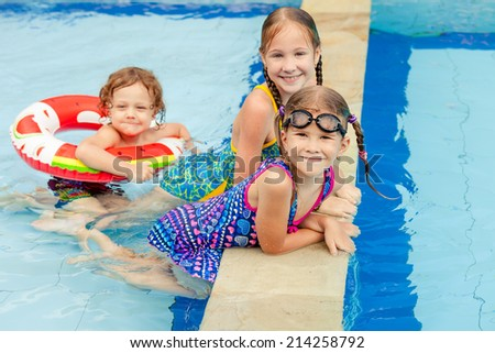 three happy little kids playing  in the swimming pool - stock photo