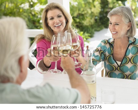 Three happy middle aged people toasting wine glasses at verandah table - stock photo