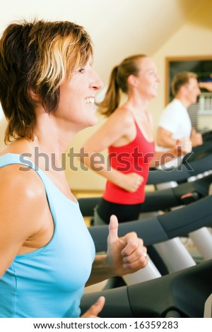 Three happy people running on a treadmill in a gym; slight motion blur on arms of woman in foreground for a dynamic picture - stock photo
