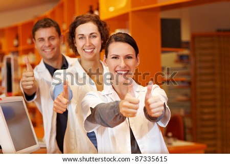 Three happy pharmacists holding their thumbs up in pharmacy - stock photo