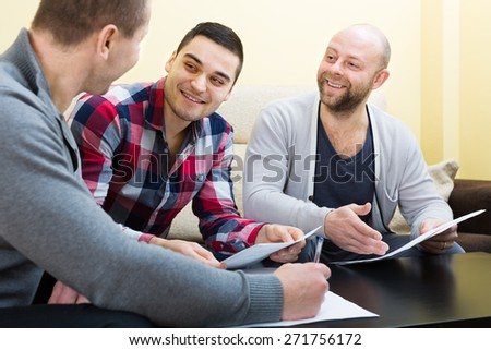 Three happy positive males with documents at agency