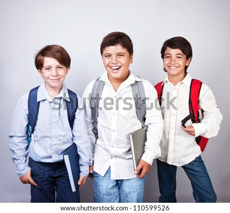 Three happy schoolboys isolated on gray&white background, back to school, best friends classmates, smiling cheerful teenagers with backpacks and books, knowledge and education concept