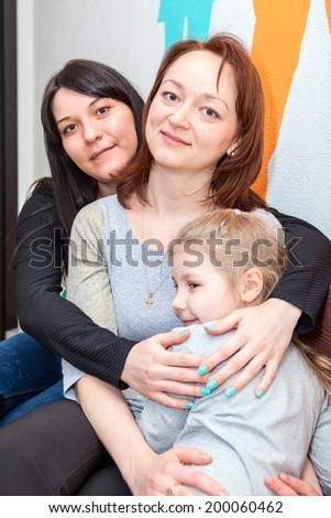 Three happy sisters different ages embracing together - stock photo